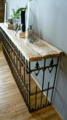 Salvaged wood & wrought iron made into a console table. Would be great as a radiator cover too!