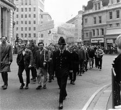 Demonstrating dock workers holding banners in support of Conservative politician Enoch Powell march past Monument in the City of London on their way...