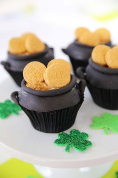 These pot of gold cupcakes are a super fun way to celebrate St Patricks Day! They really go together quite easily.  For a few more cute St. Patricks ideas check out these easy rainbow cupcakes or whip up a delicious shamrock shake. Pot of Gold Cupcake Supplies edible gold spray mist mini golden Oreos black …