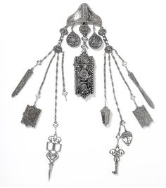 Chatelaine, Britain, ca. 1850.    Chatelaines were decorative but useful waist hung fashion accessories. The system of clips and chains, attached to the belt, kept small but necessary items such as sissors, keys and money easily accessible for housewives and housekeepers. Before the 1850s pockets were uncommon in women's garments and chatelaines were a versatile and ornamental alternative.