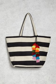A woven tote bag featuring allover stripes, dual shoulder straps, two interior slip pockets, magnetic-snap closure at the top, and multicolored tassels.