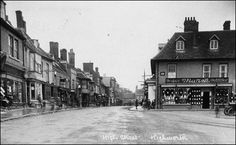 South side of High St, looking west. Notices from left to right read: The Highworth Cycle Depot, Fran New [Fishmonger/fish and chips], W L Bartrop, Dunlop Cycle Tyres, King and Queen Inn, Marsh, Draper and Outfitter. 1930s.