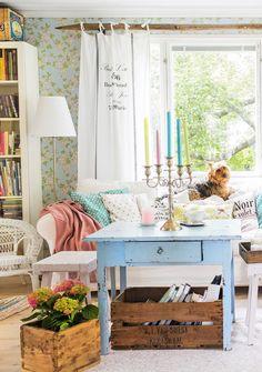 Hillityn pastellinen sisustus on levollinen. Sininen antiikkipöytä, pikkujakkarat, viinilaatikot, kukkatapetti ja heinäseipäästä tehty verhotanko sopivat yhteen.