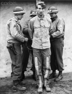 American Soldiers Preparing to Execute German Spy. American soldiers tie one of three Nazi spies to be executed to a post before a firing squad. The three German men were captured behind American lines, monitoring roads and bridges along the Meuse during the fighting in Eastern Europe.