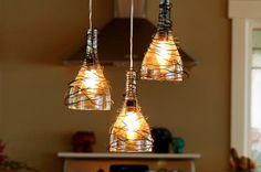 Garrafas de vinho servindo como luminárias em bancada gourmet. Ideias de iluminação e decoração reaproveitando e reciclando.