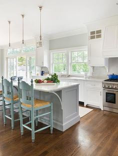 Cottage kitchen features three glass pendants illuminating a grey center island topped with white ...