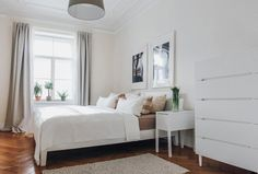 Großes, Helles Schlafzimmer In München Mit Gemütlichem Bett, Grauen  Vorhängen Und Dunklem Holzboden #