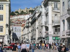 Travel Picture: Day 230. Looking down the main street of the Baixa section of Lisbon, Portugal. This car-free section of the city is just about the only flat land in an otherwise hilly city that has been compared to San Francisco. In the background is São Jorge castle.