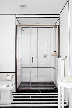 """ANN SACKS 3"""" x 6"""" Nero Marquina marble field and 9/16"""" x 8"""" box liner molding in honed finish with White Thassos 3"""" x 6"""" field in honed finish and KOHLER bancroft rite-temp pressure-balancing faucet, toilet tissue holder, towel bar, and Treshman toilet (location: Veranda show home in New York; designer: S. Russell Groves)"""