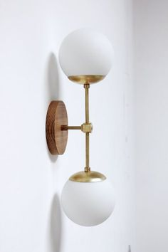 The Northern Sconce (double) is a nod to midcentury modern lighting with the large matte white glass globes and brass arms. This wall sconce is a true statement piece. -6 diameter x 1 tall oak or walnut hardwood base -Base is cut and sanded to a silky finish and sealed with beeswax -Two keyholes in back for hanging -Raw brass arms and joint -Two 7 mid century modern style matte white glass globe shades -Fixture 25 long, 8 from wall at globes -Fixture can be hardwired or built with cl...