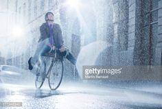 Stock Photo : Businessman riding bicycle in rainy street