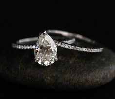 PICTURES TAKEN ON HAND ARE IN ROSE GOLD. OTHERS ARE IN WHITE GOLD. PLEASE CHOOSE YOUR GOLD COLOR CHOICE AT CHECKOUT. You are looking at a Stunning 14k Gold Solitaire Ring Featuring a Charles & Colvard Forever Classic Moissanite Pear 9x6mm. Diamonds go Half way Round the Band. This listing is for the engagement ring as well as the matching band. If you would like any other Gemstone set in this Ring, please convo me. Please read my CUSTOM ORDER Section for further information. Details: Soli...