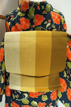芥子色のグラデーションカラーで大胆なボーダーデザインが織り出されたウールの名古屋帯です。