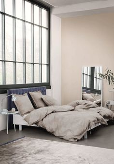 Appealing bedroom decorated in a neutral colour scheme, with a dark blue headboard as a twist. Together creates a calm look.
