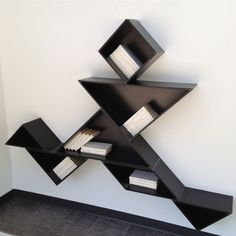 Tangram Bookshelf. A tangram is a Chinese puzzle that's made by cutting a square into five triangles, a square and a rhombus; the pieces must be arranged to form some kind of a shape. These pieces also hold your books. Cool!