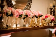 Bouquets of pink roses lined up on the mantel with glittering Mr. & Mrs. signs. Saphire Estate in Sharon, Massachusetts. Image by Meg Heriot Photography