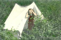 Ung stúlka, klædd smekkbuxum og stuttermabol, stendur fyrir framan tjald sem sett hefur verið upp í birkirjóðri.