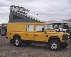 Land Rover Defender 130 caravan convert dormobile adventure camping in yellow.