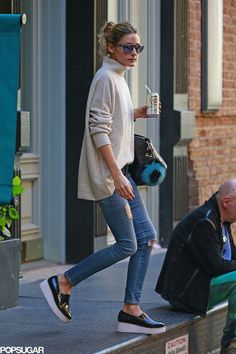 Olivia Palermo in a turtle neck sweater, distressed jeans, and platform flats.