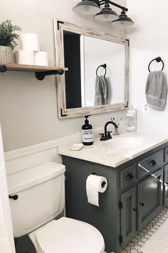 This guest bathroom uses a stunning charcoal color for its vanity. The color is trendy, modern and it's now. The floating shelf with the rustic mirror throw in some farmhouse flare. White hexagons on the floor add some depth and texture to the space. Upstairs Bathrooms, Downstairs Bathroom, Master Bathroom, Boho Bathroom, Small Bathroom Redo, Charcoal Bathroom, Bathroom Vanity Makeover, Bathroom Showers, Ikea Bathroom