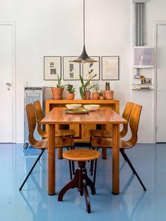 """.De jacarandá, o banco faz bonito na cabeceira da mesa da mesma madeira (ambos da Loja Teo). Os bowls de cerâmica (Olho Interni) e o pendente (Reka) arrematam a cena. """"Vibrante sem ser cansativo, o azul realça as plantas, os móveis e a luminosidade que banha os espaços"""", conta Rodrigo."""