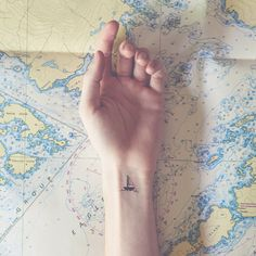 """In his clever photo series """"Tiny Tattoos,"""" photographer Austin Tott pairs whimsical miniature tattoos to matching background scenes."""