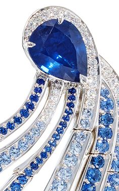 CLOSE UP: These scintillating earrings feature round brilliant diamond and lavish blue sapphire embellishments in intricate curvilinear designs.