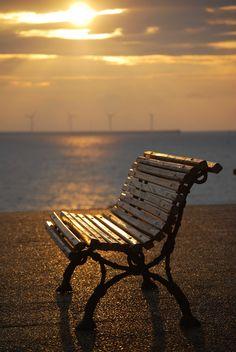 Una tarde de viento, vestida de nubes en tonos grises, lució, para despedirse, una gargantilla dorada que dejó recostada sobre el banco ya vacío. Se fue a dormir desnuda con un mar que le esperaba sereno y azul. El banco durmió solo.
