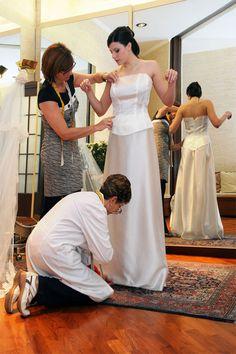 Cinzia Ferri e una sarta lavorano il vestito su una sposa.