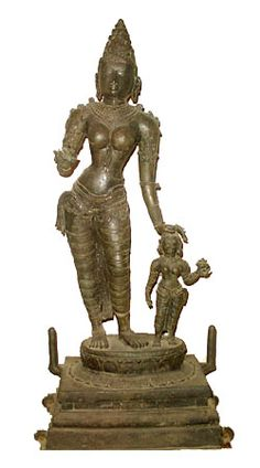 Parvati with attendant, Tiruvengimalai, Trichy District. Height 92cm. 10th Century. Parvati stands in a tribhanga with an attendant. A masterpiece of Chola art! She stands on an oval padmasana over a rectangular bhadrasana. Her right hand is in the posture of holding a flower and her left hand is placed on the head of her dwarf attendant (Vamanika). The modeling of the breasts, the disposition of the hands, especially that of the left hand display a gentle frailty.