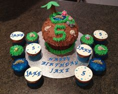 Giant chocolate reptile theme cake with hand made palm tree and rocks and edible blue gel for water Matching cupcakes Follow me on Facebook .. The Cupcake Home