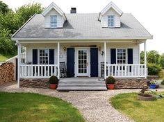 Die Veranda an der Front verläuft über die gesamte Breite des Hauses. Typisch für amerikanische Häuser sind außerdem Schiebefenster und eine horizontale Holzverschalung.