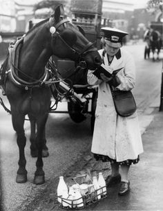 WWII Shopping and Food, England- A female milkman makes an entry in a notebook, with a horse beside her.