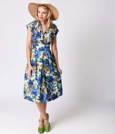 Flora is an enchanting 1930s inspired frock with a draped v-neckline and grown on cap sleeves, complete in a breathtaking blue blossoming poppies print. The semi-full pleated skirt features a high, curved waistband that rests flat on the hips, with concea