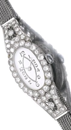 ART DECO GEM SET AND DIAMOND JEWELS, 1920S    A lady's wristwatch, the oval dial applied with Arabic numerals, the bezel and shoulders pierced and millegrain-set with circular-cut diamonds, strap adjustable, maximum length approximately 180mm.