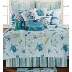This coastal theme quilt features sea turtles,se ahorses, starfish in shades of blue and a touch of green on a pale aqua background. Relaxing colors for a beach bedroom decor.
