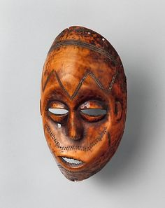 Lega mask (Bwami, Lukungu), ivory - The masks refer to ancestors and are passed from one generation of initiates to the next as symbols of continuity. For the Lega, physical beauty and moral excellence are inseparable. The dotted-circle motifs on many Lega works represent body markings, which enhance both the carvings and the characters they depict. The smooth polished surfaces of these sculptures allude to the refined and perfected nature of the Bwami initiate.