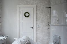 Olen juuri tapetoimassa salin muuriseinää harmaalla Toile de Jouy -tapetilla. Minusta näyttää siltä, että jo nyt kakluuni ja kylpyhu...