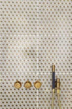 gold and white wall tiles, brass shower fittings
