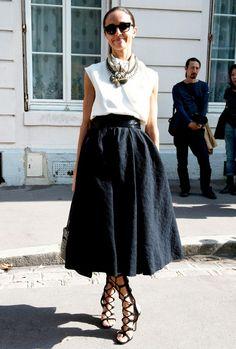 Voluminous skirt, gladiator heels, necklaces.