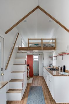 The kitchen features white cabinets, open shelving, and oak countertops.