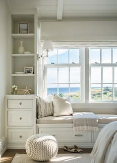A white built-in window bench is placed in a recessed niche of a cottage-style master bedroom topped with beige linen cushion, accent pillows, and fringe throw.