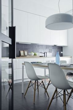 Smithfield by Jasper Morrison for FLOS matches the simple, modern decor in this kitchen interior featuring white settings.