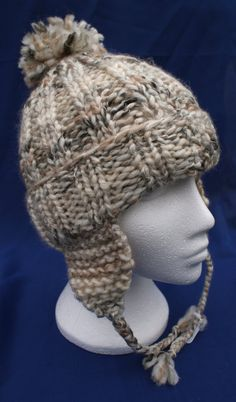 Hand knit woolly earflap hat with bobble in Oatmeal. Warm winter hat for teens Hand knit woolly earflap hat with bobble in Oatmeal. Warm winter hat with braids, plaits. Hat for teens Hot Buttered Rum, Baby Turban, Warm Winter Hats, Angora, Chunky Wool, Plaits, Knitting For Beginners, Crochet Accessories, Hats For Women