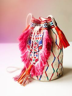 59a9e089f9a Tribal-inspired bucket style bag featuring colorful bead and fringe  accents. Leather trim with