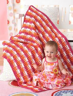 Are you in need of an easy crochet baby blanket? Look no further than the Bright and Bold Crochet Baby Blanket. Using the crochet treble stitch to create its unique dripping lines appearance, this crochet baby blanket is definitely fit for a modern or contemporary nursery.