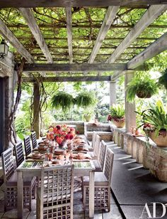 Kiwi vines shade a terrace furnished with a Charles Rennie Mackintosh–style teak table and chairs by R. L. White and Son | archdigest.com