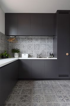 In this modern laundry room, matte black cabinets provide a strong contrast to the light grey tiles and the white countertops. A drying bar has been i… – Laundry Room Modern Laundry Rooms, Laundry Room Layouts, Modern Room, White Kitchen Backsplash, White Countertops, Backsplash Ideas, Interior Design Kitchen, Home Design, Condo Kitchen Remodel