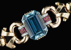 A 46 carat large emerald cut aquamarine with an even blue color nestled between dimensional oval links and scrolls attached with a band set with rows of rubies and diamonds. A double row of snake chains finishes the bracelet. Hand fabricated from heavy gauge gold the high quality of the fabrication indicates a top maker.  Image courtesy of Lang Antiques  File:Aqua2.jpg - Antique Jewelry University