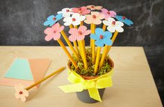 """Crafty Gift Idea for a Student, Teacher, or """"New Office""""... - Paint a small terracotta planter with chalkboard paint & add a pretty ribbon - Fill with foam & top with a bit of raffia or faux grass - Add in pens or pencils decorated with paper/silk flowers, bling, or any other decorative element"""